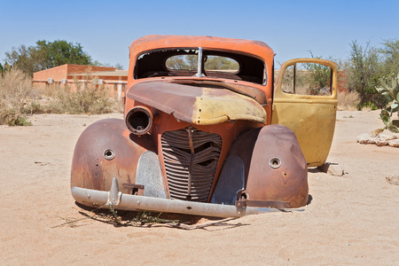 abandoned: Old rusted car in front of the gas station Solitaire, Namibia Stock Photo