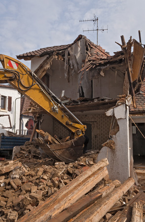 tearing down: A large track hoe excavator tearing down an old house