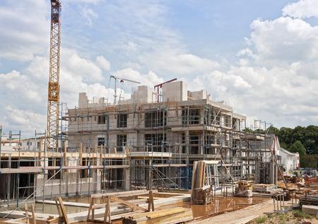 construccion: emplazamiento de la obra con la grúa y un nuevo edificio