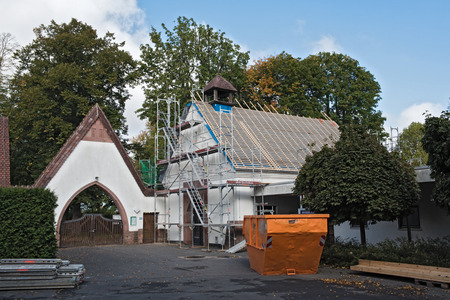 Roofers rehabilitate the roof of a cemetery chapel