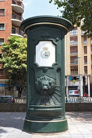 green iron drinking water fountain with lion head in downtown bilbao spain Редакционное