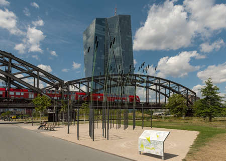 Deutschherrnbruecke with red train in front of the european central bank (ecb) in frankfurt am main, germany