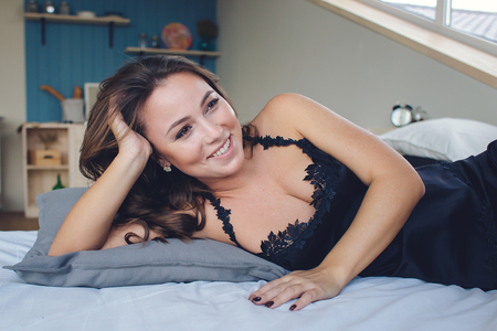 Pretty young smiling woman in lingerie lying on bed.