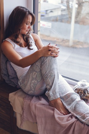Beautiful young woman with long brunette wavy hair sitting on window sill in room with white wall. Shes enjoying morning time. Wearing nice pajama.