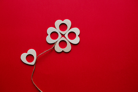Valentines flower made of heart-shaped of wood billet on red background