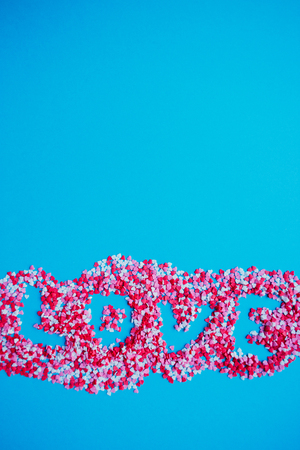 Love word shape from hearts candy sprinkles over turquoise Stock Photo
