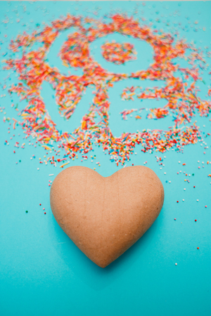 Love word shape from hearts candy sprinkles over turquoise, papier mache