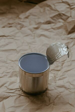 Used iron tin can on a plain crumpled brown kraft paper background. Environmental pollution concept, used trash. Copyspace. Banque d'images