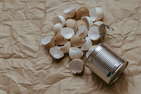 Eggshell in tin top view. Creative still life photo of an Eggshell in a tin can on brown background.