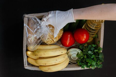 A hand in a rubber glove holds tomato. A donation box with a food. Fruits, vegetables, canned food, pasta and sunflower oil in a box. Social assistance with food.