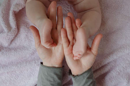 Baby feet in mother hands. Mom and her Child. Masseur massaging little baby's foot. Happy family concept. Beautiful conceptual image of maternity