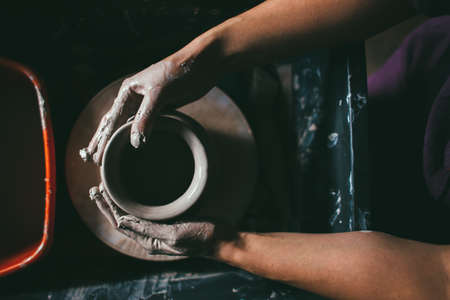 Man hands making clay jug macro. The sculptor in the workshop makes a jug out of earthenware closeup.