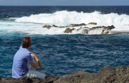 Young man in blue shirt sitting on rock shore and looking at ocean. View from behind. Background of blue ocean with high waves, seafoam and splash of water Imagens