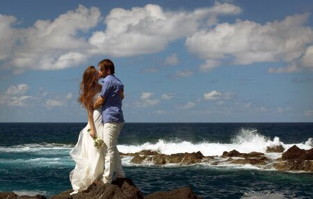 Young just married couple kissing on ocean rock shore. Side view. Ocean waves, splash of water and blue cloudy sky.