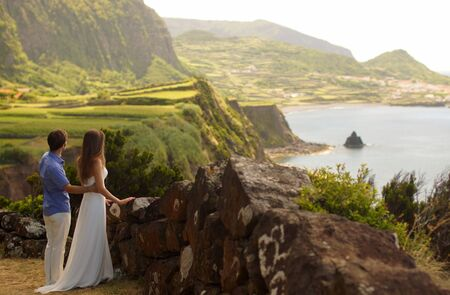Young newly wedded couple standing on ocean coast. Young man hugging woman in white dress. Romantic idyllic landcsape