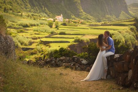 Young newly wedded kissing couple. Attractive woman in white dress hugging man. Romantic background of idyllic landcsape