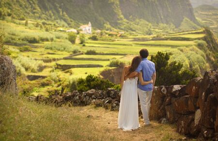 Young newly wedded couple hugging each other. View from behind. Background of romantic idyllic green landcsape