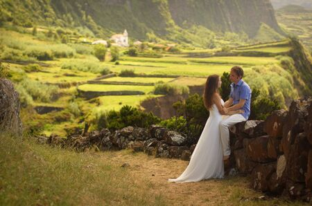 Young newly wedded hugging couple. Attractive woman in white dress with man. Romantic background of idyllic landcsape