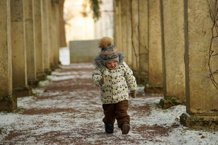 Little boy with red cheeks, in bright clothes and mittens walking up the path and looking down in snowy winter park 스톡 콘텐츠