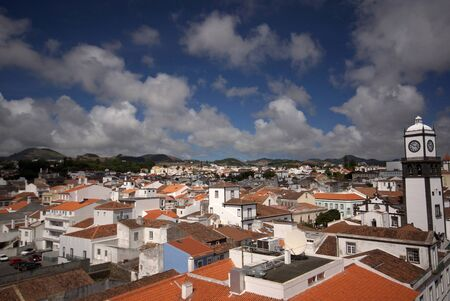 Multicolored view of of Ponta Delgada city on Sao Miguel island, Azores. Red roofs, white houses on background of blue cloudy sky and mountains Stock Photo