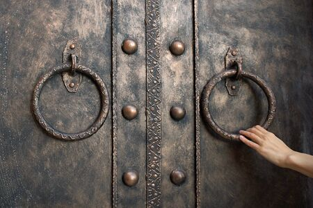 Closeup photo of single elegant womans hand holding metal ring of iron entrance door on brick wall 스톡 콘텐츠