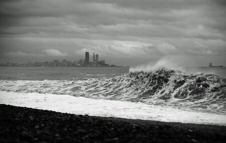 Impressive view of splashing storm with big waves hitting the sea coast in the evening. Background of mountains, Batumi city, Georgia. Black and white photo
