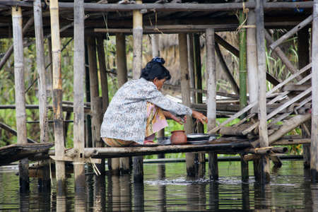 Nyaungshwe Inle Lake, Burma - December 4, 2012. woman washing dishes in lake water on staircase of bamboo house on piles Editorial
