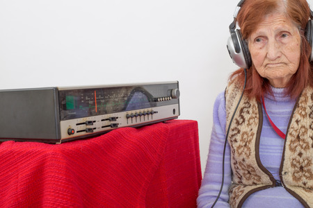 oldie: Elderly lady listening attentively radio with headphones. Stock Photo