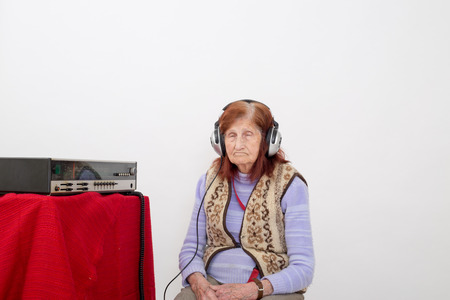 analogical: Elderly lady listen carefully radio in her sleep with headphones.
