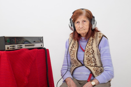 analogical: Elderly lady listening attentively radio with headphones. Stock Photo