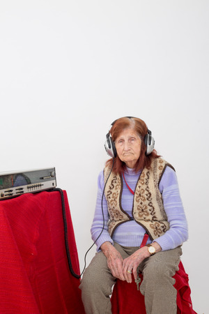 attentively: Elderly lady listening attentively radio with headphones. Stock Photo