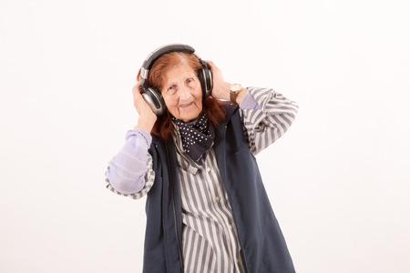 funny elderly: Funny Elderly lady listening music with headphones Stock Photo
