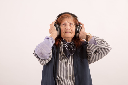 analogical: Funny Elderly lady listening music with headphones Stock Photo