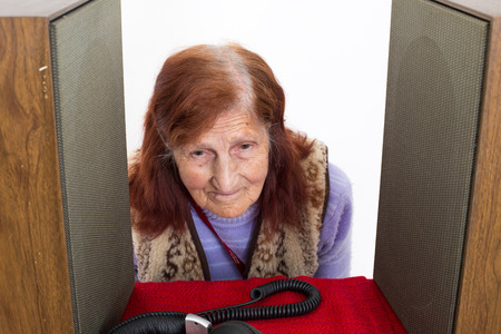 analogical: Elderly lady putting her head  between Audio Speakers to hear better Stock Photo