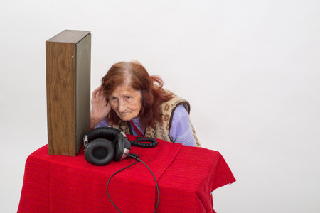 analogical: Elderly woman with the hand on her ear, trying to hear radio Stock Photo