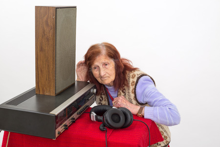 seniority: Elderly woman with the hand on her ear, trying to hear radio Stock Photo