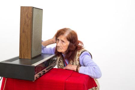 seniority: Elderly lady listening attentively to the old radio.
