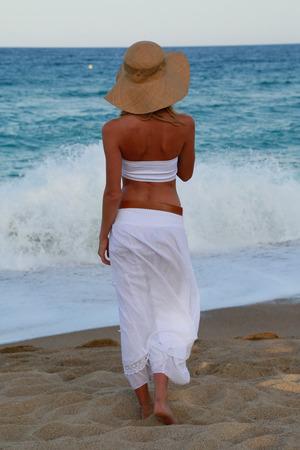 fervor: Young girl in hat walking along the beach