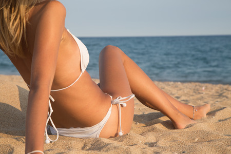 petite fille maillot de bain: Belle fille couch�e sur la plage avec la mer en arri�re-plan, Bodyparts