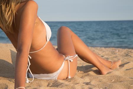 niñas en bikini: Muchacha hermosa que miente en la playa con el mar de fondo, Bodyparts