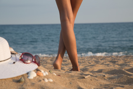 bodyparts: Legs of a girl on a beach with sea in background, Bodyparts