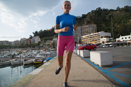 lycra: Young woman jogging in harbor in colorful sportwear.