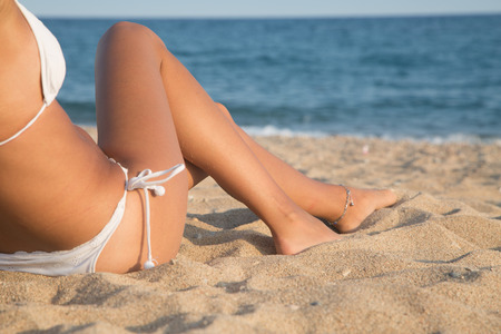 bodyparts: Beautiful girl lying on the beach with the sea in background, Bodyparts