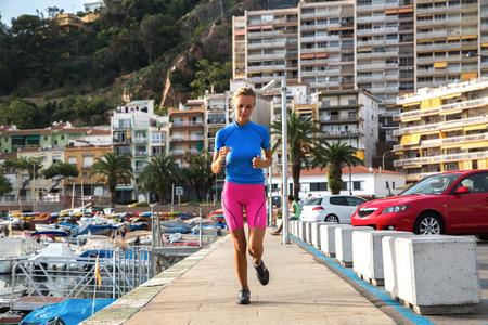 sportwear: Young woman jogging in harbor in colorful sportwear.