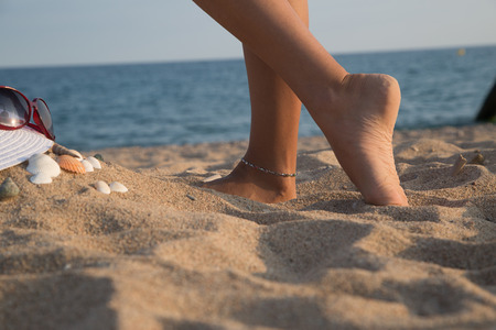 bodyparts: Feet of a girl in the sand on the beach with sea in background, Bodyparts