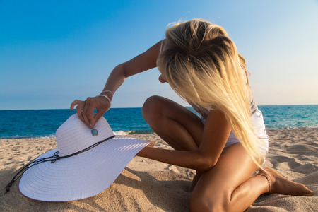 decorates: Photographer at work, girl decorates hat on the beach. Stock Photo