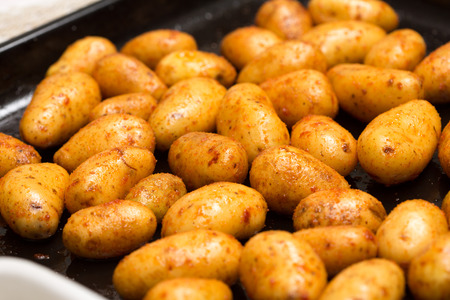 oiled: Shiny fresh, oiled potatoes on an oven plate Stock Photo