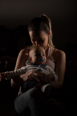 single mother: Overtired single mother with her baby