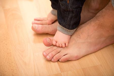 padres: Padre ayudando a su hijo durante los primeros pasos.