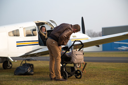 monoplane: Happy family with child before flight.